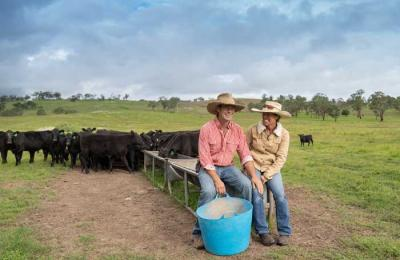 A photo of Stu and Erica Halliday sitting on a cattle feeder